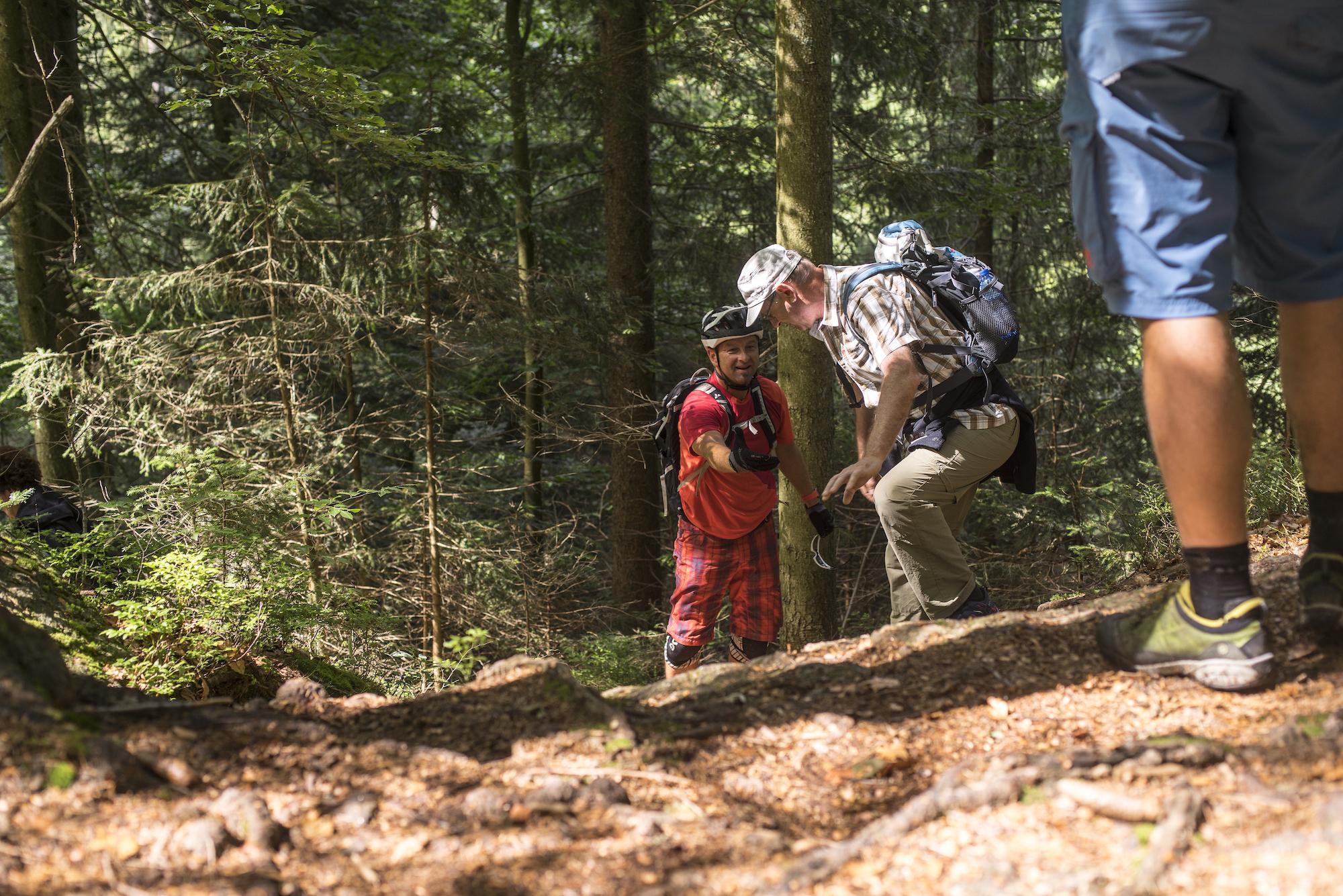 Mountainbiker und Wanderer geben sich die Hand - sie interagieren. Diese Begegnung ist nicht planbar, mit einem touristischen Produkt ist ihr Zustandekommen aber wahrscheinlicher.